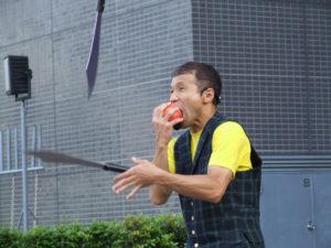 コメディーパフォーマーのミスターウキウキが剣をまわしながらリンゴを食べる